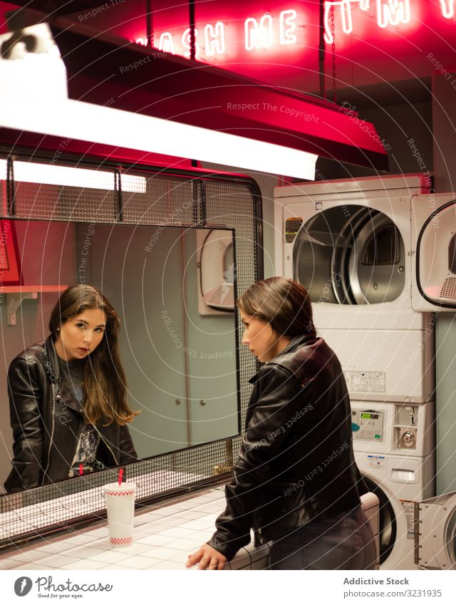 Sorglose Frau mit Getränk in modernem Waschsalon warten Magazin trinken Öffentlich Dienst Erfrischung lesen Imbissbude cool Einrichtung Dienstprogramm Stroh