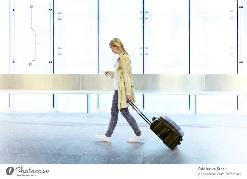 Reisende Frau mit Gepäck zu Fuß im Flughafen Smartphone Tourismus Passagier Gerät Mobile Apparatur Koffer benutzend Terminal Internet Ebene online reisen