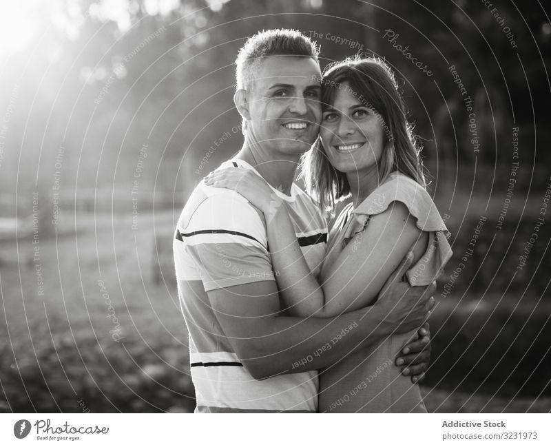 Paar, das mit glücklichem Lächeln in die Kamera schaut Liebe Glück Urlaub sonnig tagsüber Mann Frau Erwachsener Flitterwochen Sommer Natur Ufer Küste