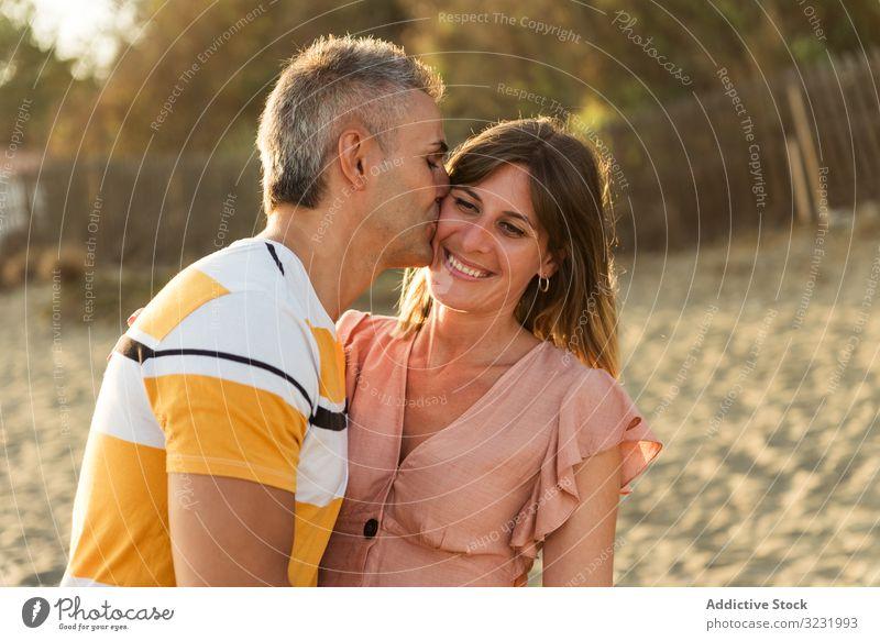 Lachendes Paar umarmt sich am Sandstrand Strand Resort Lächeln Glück Umarmung Spaß Liebe Urlaub sonnig tagsüber Mann Frau Erwachsener Flitterwochen Sommer Natur