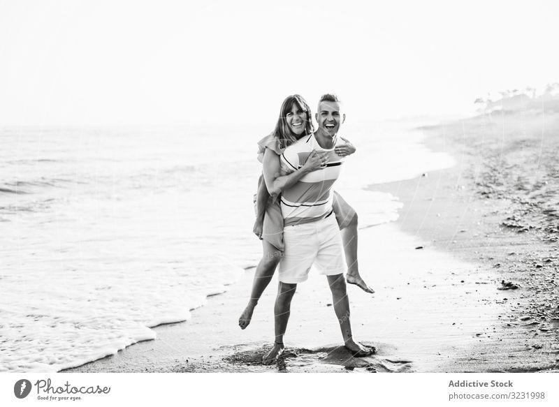 Mann trägt Frau auf dem Rücken in Meeresnähe Paar Strand Resort Liebe MEER Huckepack Mitfahrgelegenheit Lächeln Glück Urlaub Spaß winken Wasser Erwachsener