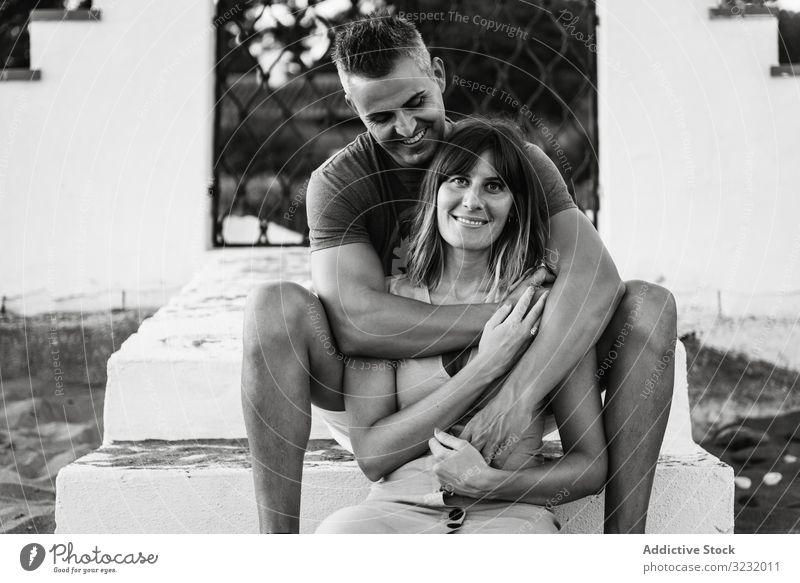 Erwachsenes Paar umarmt sich auf Stufen Liebe Umarmung Freitreppe sitzen Lächeln Erwachsener Gebäude Partnerschaft Glück Mann Frau Zusammensein Lifestyle