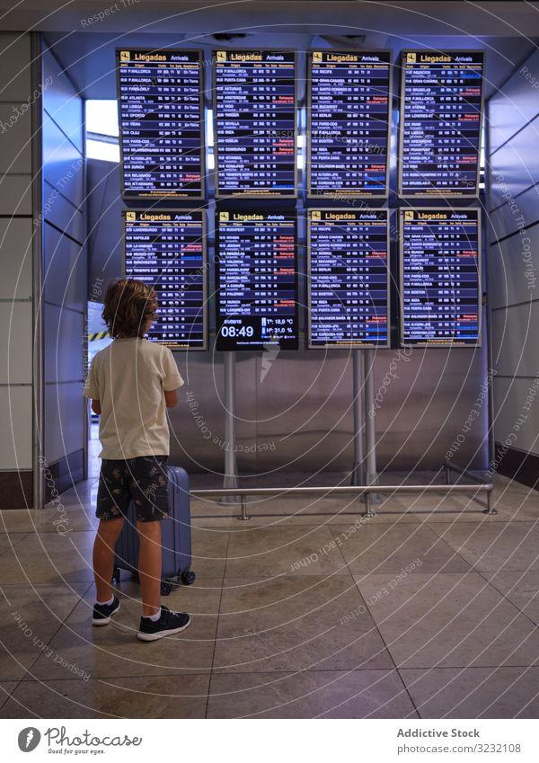 Leseprogramm für Kinder in der Halle des Flughafens Junge Koffer Anzeigetafel Aussehen lesen Zeitplan Saal Portugal reisen Tourist Gepäck Abheben Ankunft