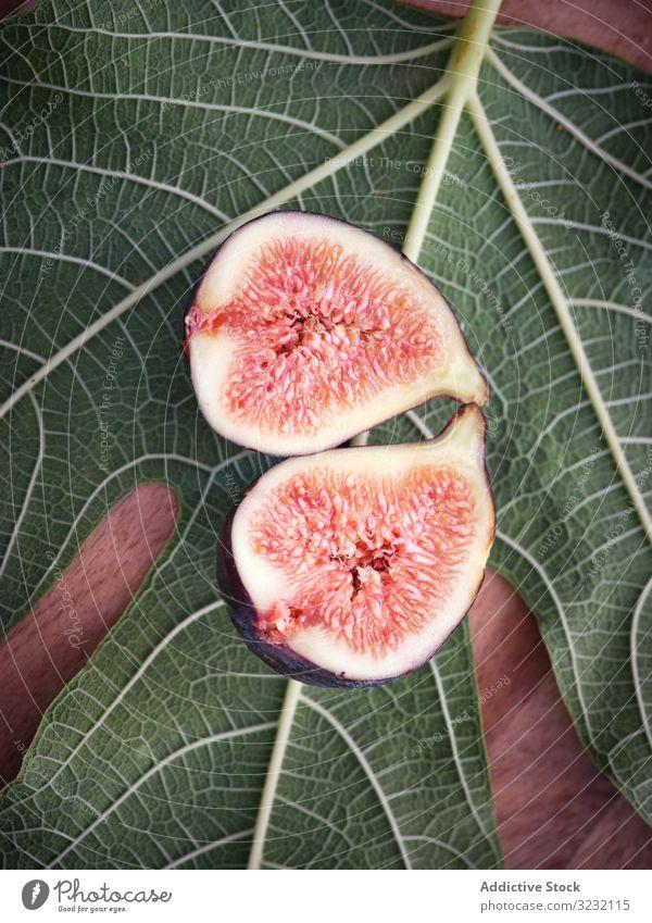Feigenstücke über Tisch und grüne Blätter Blatt reif rustikal frisch Früchte ländlich Baum Lebensmittel hölzern traditionell Nahaufnahme Spanien heimwärts