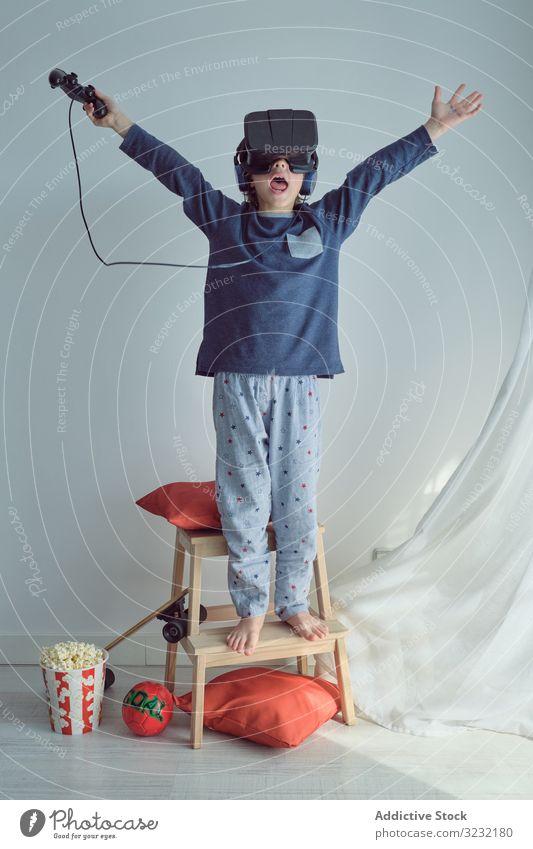 Glückliches Kind im VR-Headset spielen Schutzbrille gewinnen Joystick Tor Sport Popkorn Freizeit Spaß Arme hochgezogen so tun, als ob Spiel Wochenende Simulator