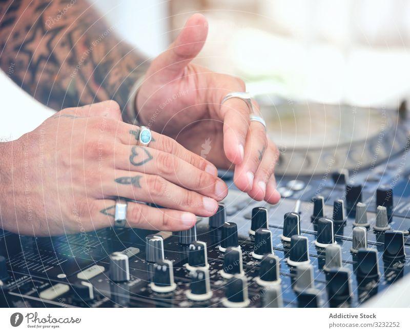 Anonymer DJ, der während der Party Musik auflegt dj Melodie Audioboard Mixer Arbeit Tattoo Club Schauplatz Ringe Entertainment Klang Schaltfläche drehen. Hand