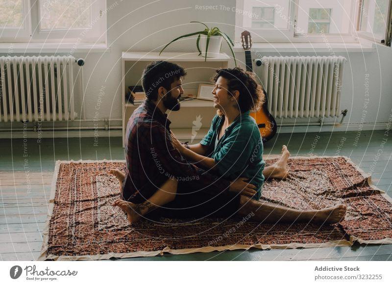 Liebespaar umarmt sich, während es auf dem Boden einer Wohnung sitzt Paar Umarmen Stock Appartement sitzen liebevoll Kuscheln Angebot lässig Lächeln Teppich