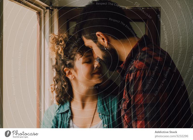 Glückliches Paar umarmt sich zu Hause auf der Fensterbank Umarmen Fenstersims heimwärts freudig Lächeln lässig Umarmung Hipster modern Angebot Zuneigung