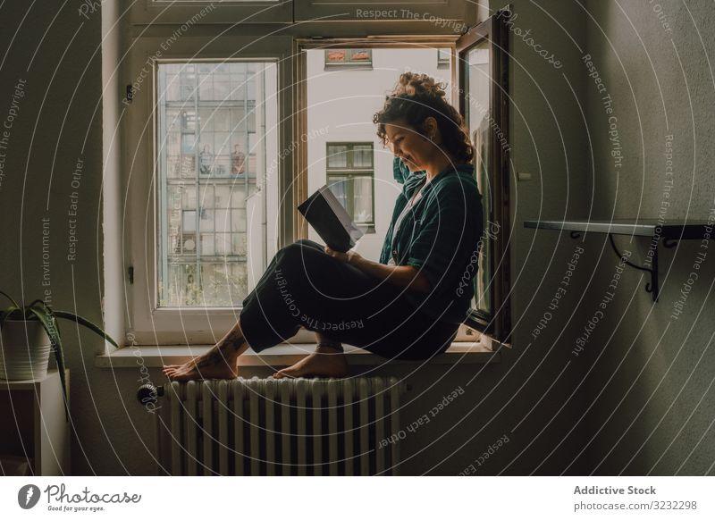Interessierte Frau liest zu Hause am Fensterbrett lesen heimwärts Buch interessiert entspannt Literatur Fenstersims Barfuß lässig sitzen Appartement Glück