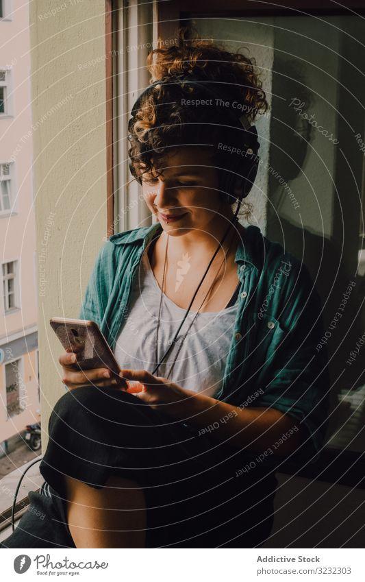 Fröhliche Frau mit Kopfhörern, die zu Hause ein Smartphone benutzt heiter Lächeln benutzend zuhören Glück Musik Browsen Fensterbrett lockig attraktiv friedlich