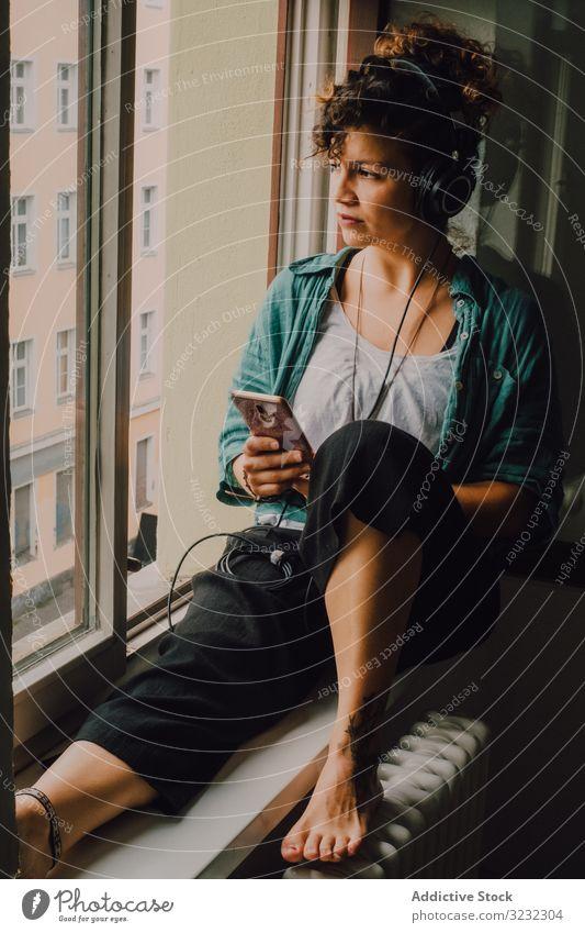 Entspannte Frau mit Kopfhörern und Smartphone zu Hause Lächeln benutzend besinnlich zuhören Glück Musik Browsen Fensterbrett lockig attraktiv friedlich