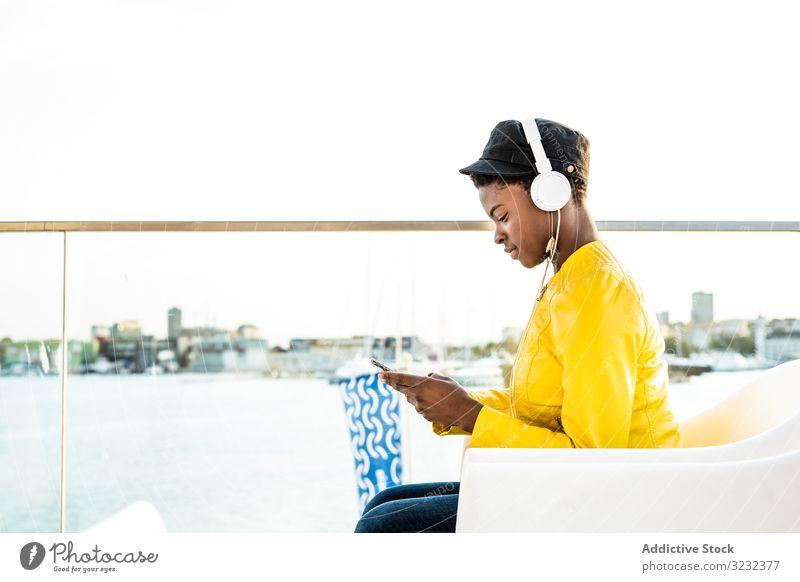 Schwarze Frau benutzt Mobiltelefon stylisch Afroamerikaner Jacke hell niedlich attraktiv positiv Gesundheit jung hübsch modern heiter sich[Akk] entspannen Kälte