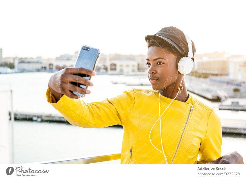 Schwarze Frau benutzt Mobiltelefon stylisch Afroamerikaner positiv jung hübsch modern heiter sich[Akk] entspannen Schönheit ethnisch schwarz Textfreiraum cool