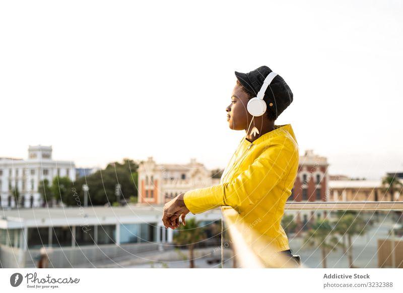 Friedliche Frau genießt Musik und entspannt sich auf dem Balkon Kopfhörer friedlich Inhalt trendy Afroamerikaner sich[Akk] entspannen fettarm Glas genießen