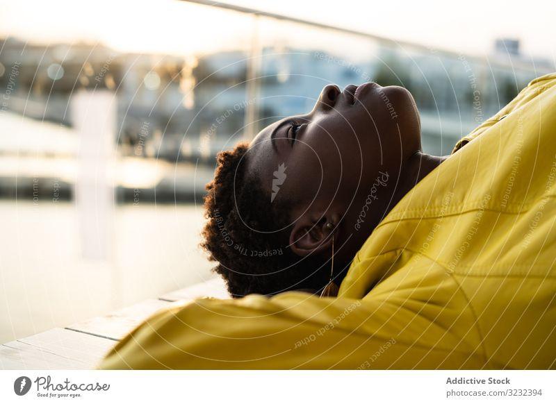 Frau chillt auf der Bank stylisch Kälte sich[Akk] entspannen modern klug hölzern Jacke Afroamerikaner jung cool trendy Glück Zeitgenosse Treffpunkt niedlich