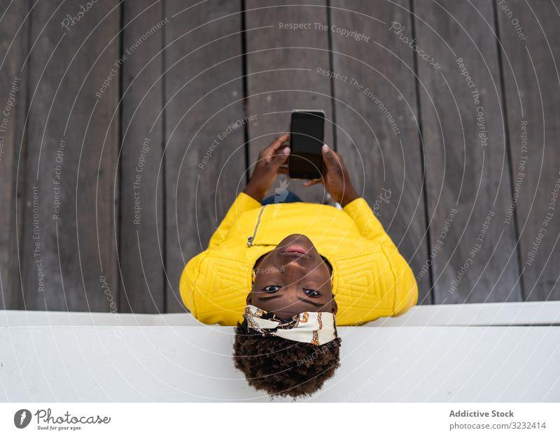 Ruhige Frau benutzt Mobiltelefon modern sich[Akk] entspannen fettarm Großstadt Straße ruhig Afroamerikaner Wand Gebäude jung Freizeit Glück Denken Kontemplation