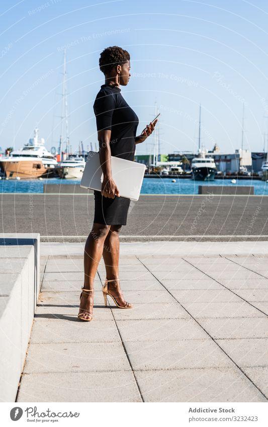 Schwarze Frau benutzt Mobiltelefon auf der Straße Laptop sich[Akk] entspannen benutzend Surfen Afroamerikaner modern elegant Kleid schwarz Gebäude Straßenbelag