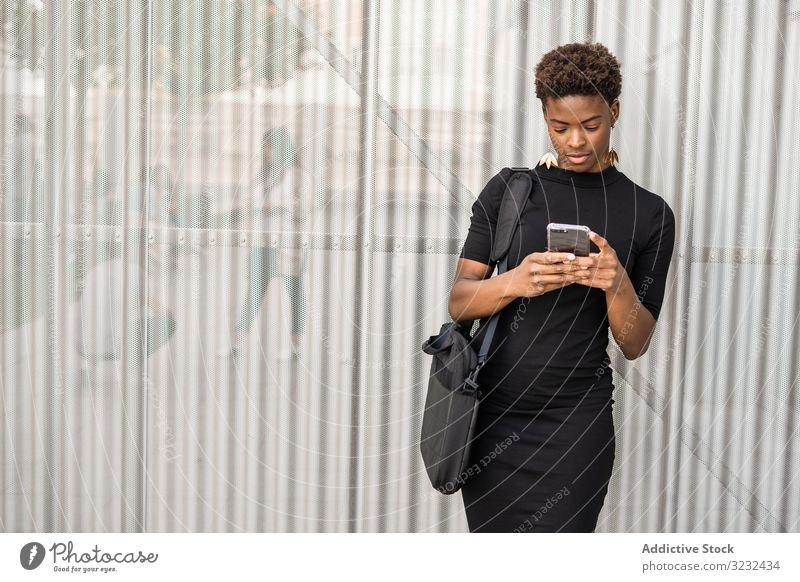 Konzentrierte weibliche Nutzung eines Mobiles in der Nähe eines städtischen Gebäudes Frau Smartphone Nachricht Straße urban benutzend Afroamerikaner fokussiert