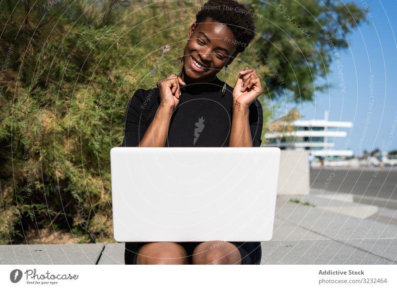Seriöse Frau surft am Laptop in der Nähe eines modernen Gebäudes sich[Akk] entspannen konzentriert benutzend Surfen Afroamerikaner elegant Straße Kleid schwarz