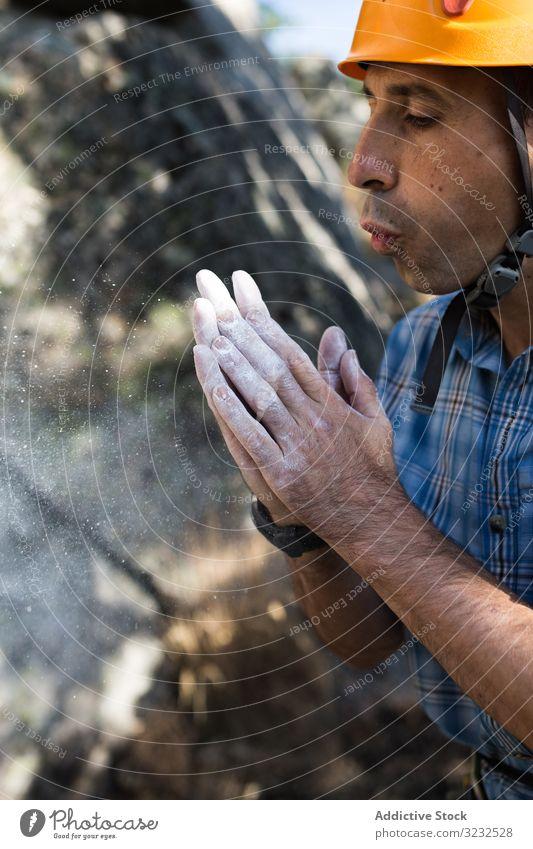 Bergsteiger bläst Kreidepulver aus seinen Händen Sport Bergsteigen Mann Adrenalin schwierig Stärke stark sportlich Person Aufstieg Abenteuer Natur Training