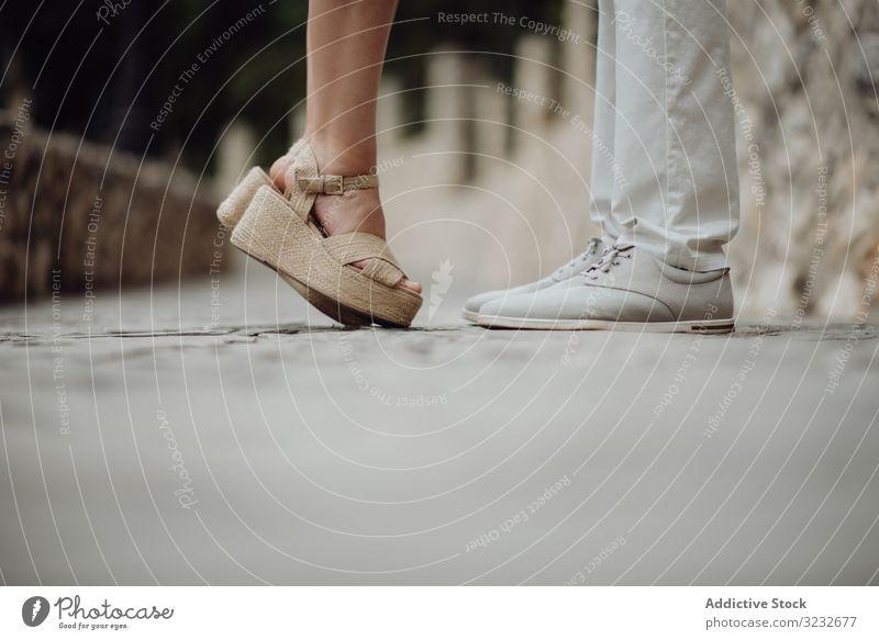 Romantisches Paar steht sich an der Sommerstraße gegenüber romantisch Straße Kuss Kieselstein Valentinsgruß Straßenbelag auf Zehenspitzen Sandalen stehen