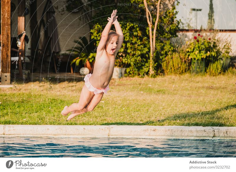 Fröhliches Mädchen springt in den Pool springen Wasser schreien angehobene Arme Spaß Hof spielen Kind wenig Hände hoch Frauenunterhose ohne Hemd Garten Urlaub