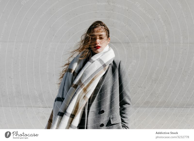 Junge Frau in Mantel und Schal an windigem Tag stylisch Straße geschlossene Augen Wand Großstadt Gebäude urban Mode cool jung Model Outfit warm Wetter