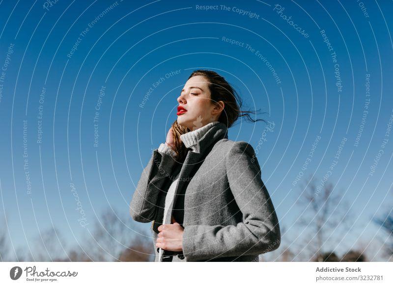 Junge Frau im Mantel an windigem Tag stylisch Straße geschlossene Augen Mode cool jung Model Outfit warm Wetter Außenseite Dame lange Haare trendy elegant