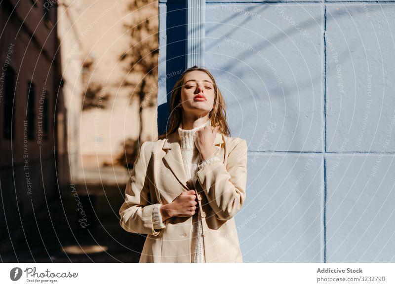 Sinnliche Frau steht blaues Gebäude auf der Straße stylisch sonnig Schutz jung sinnlich urban Mode Model cool trendy Deckung Bluse elegant Dame Außenseite