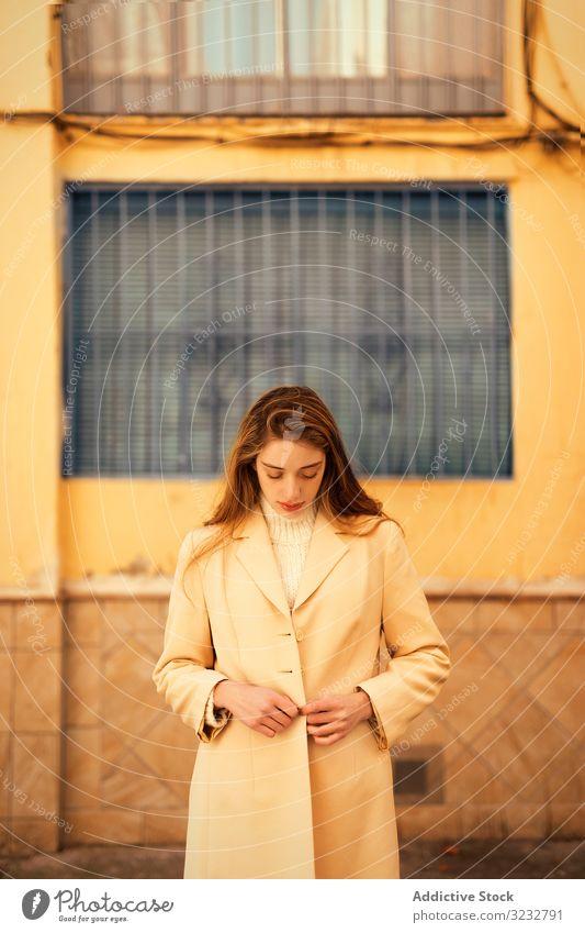 Junge Frau knöpft ihren Mantel auf der Straße zu stylisch Schaltfläche sinnlich Großstadt jung Mode elegant Model Outfit lange Haare trendy Glamour Gebäude