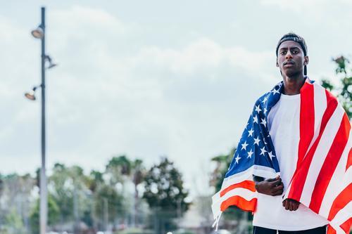 Schwarzer Mann wickelt sich draußen in amerikanische Flagge ein Amerikaner Fahne eingewickelt schwarz Afroamerikaner national Selbstständigkeit aktiv 4. Juli