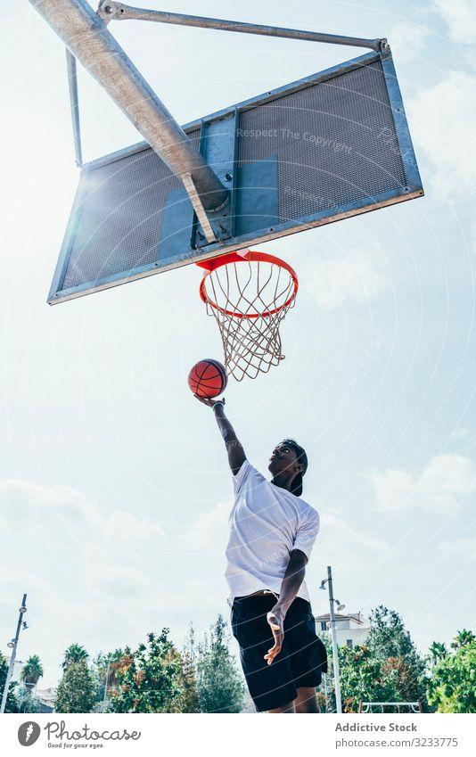 Afroamerikanischer Sportler hängt auf Basketball-Runde Ball tretend Netz Slam Dunk Spiel Spieler Stadion Spielen Sportbekleidung Aktivität Feld männlich