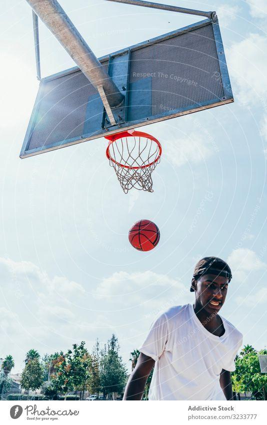 Afroamerikanischer Sportler nach Treffer im Basketball Ball tretend Netz Slam Dunk Runde Spiel Spieler Stadion Spielen Sportbekleidung Aktivität Feld männlich