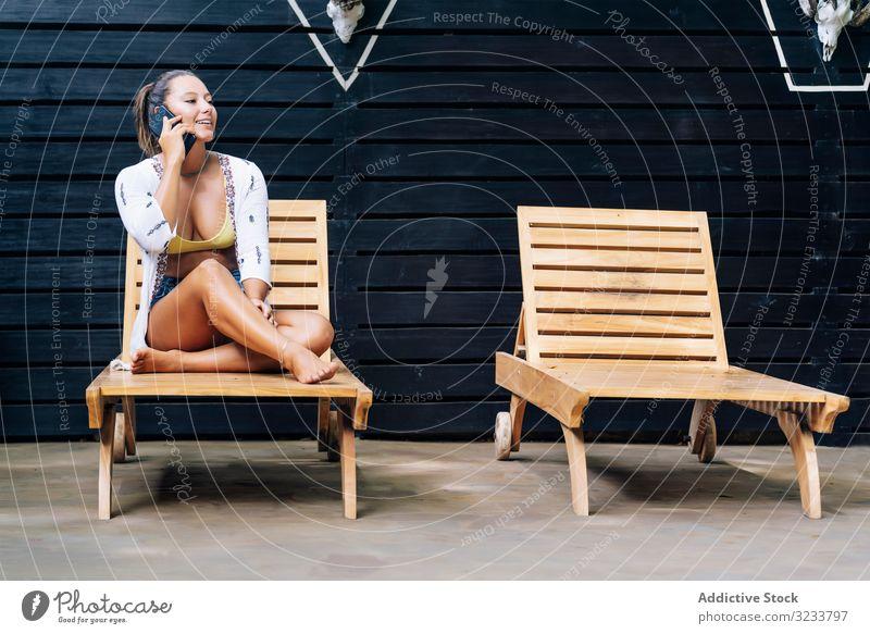 Entzückte Frau telefoniert, während sie sich auf einem Liegestuhl ausruht reden Handy erfreut Glück Lächeln sprechen Smartphone benutzend ruhen sitzen lässig