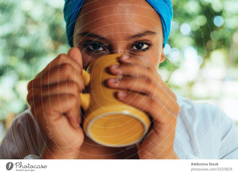Frau im Turban beim Kaffeetrinken ruhen patio zufrieden Lächeln Inhalt genießen Starrer Blick Baum Kopfverpackung ländlich Costa Rica Grün Glück jung Terrasse