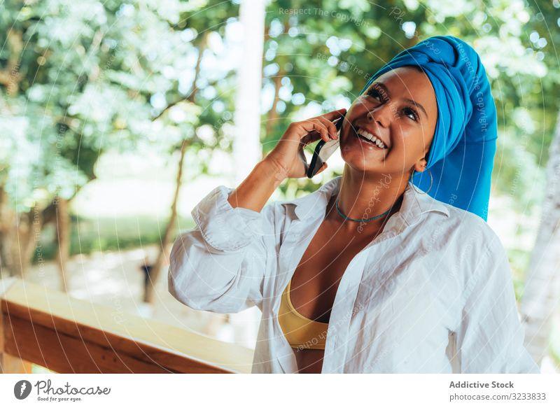 Frau mit Turban spricht am Mobiltelefon positiv Lächeln Smartphone benutzend Kopfverpackung Bräune attraktiv farbenfroh Grün jung Glück Spaß Foto Costa Rica