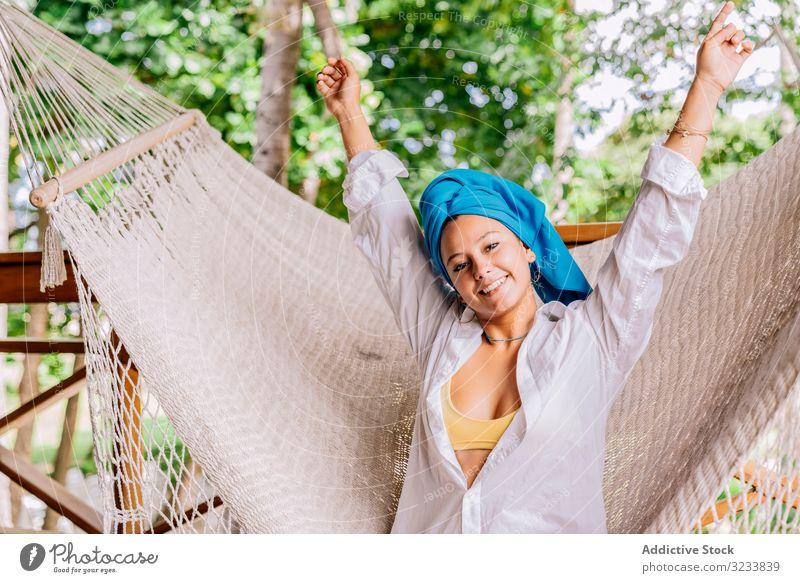 Vergnügte Frau im Turban ruht sich in Hängematte auf Terrasse aus ruhen Glück Lächeln Handerheben sitzen Baum Grün Hemd friedlich Costa Rica jung