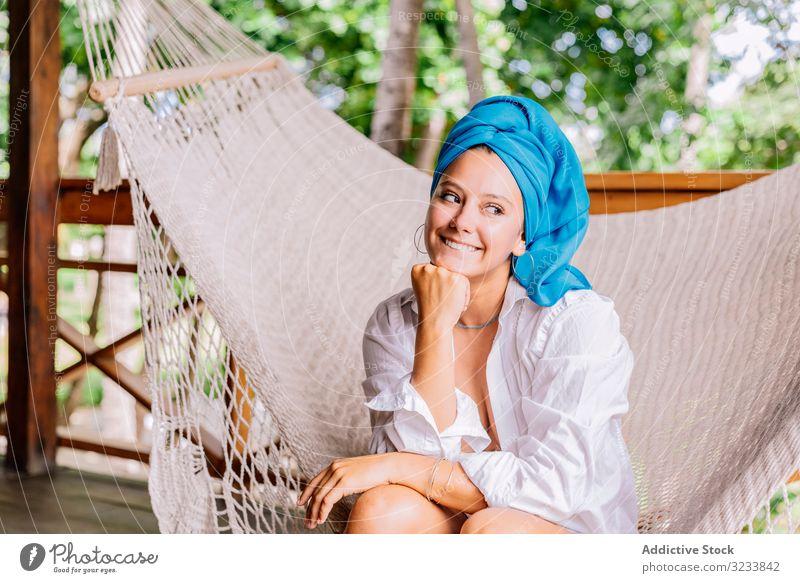 Frau mit Turban ruht sich in Hängematte aus ruhen Glück Lächeln berührendes Gesicht sitzen Terrasse Baum Grün Hemd friedlich Costa Rica jung