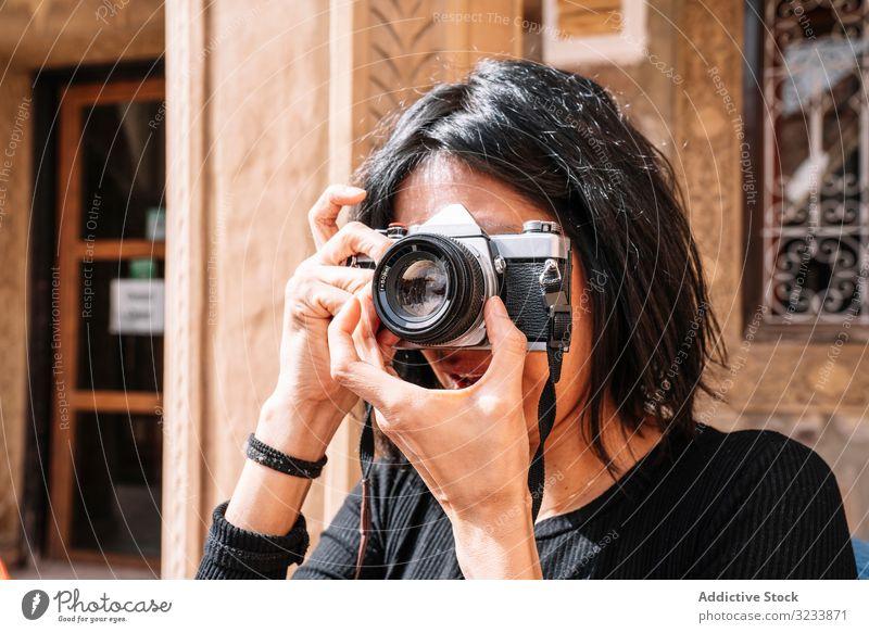 Weibliche Fotografin, die auf der Straße mit der Kamera fotografiert Fotokamera fotografierend Frau positiv Lächeln lässig Einstellung benutzend Optik sitzen