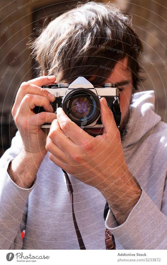 Männlicher Fotograf, der mit einer Kamera auf der Straße fotografiert Fotokamera fotografierend Mann positiv lässig Einstellung benutzend Optik jung Erwachsener