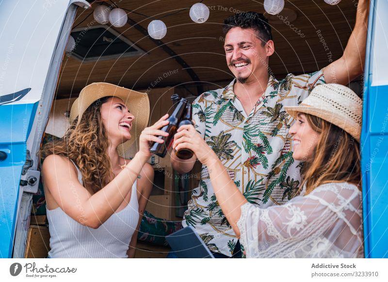 Lächelnde Freunde klirren an Bierflaschen und feiern Urlaub Flasche klirrend trinken PKW Minivan Frauen reisen Alkohol Getränk Party Straße zeigend Zusammensein
