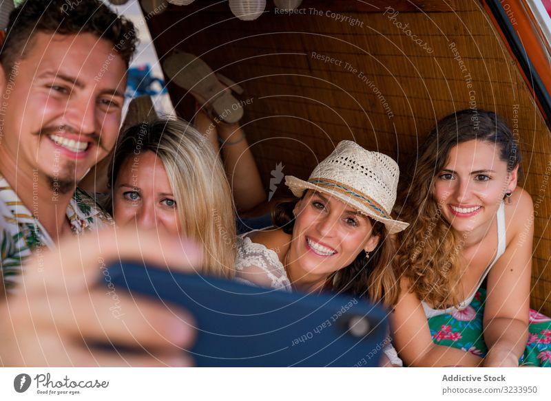 Lächelnder Mann nimmt Selfie mit Freundinnen, die sich bequem auf den Kofferraum eines blauen Autos legen Menschen Selfie nehmen Smartphone PKW Seeküste Freunde