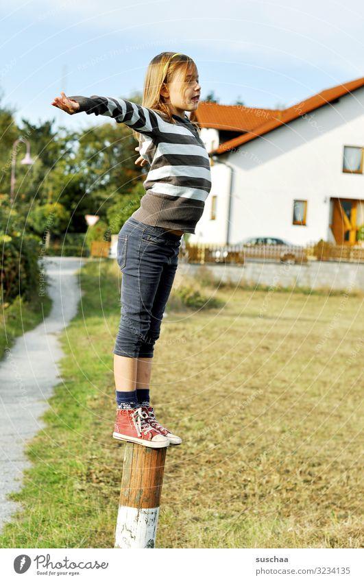 kletterin (geschafft) Kind Mädchen jungennhaft Klettern Spielen gewagt Pfosten Holzpfahl Zaunpfahl Außenaufnahme Fußweg Haus Dorf Gebäude Wohnhaus Natur toben