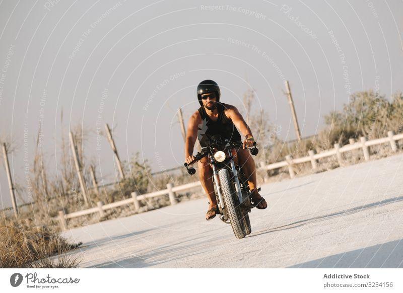 Selbstbewusstes männliches Motorradfahren Mann Schutzhelm moto Laufwerk Sonnenbrille erfreut selbstbewusst sitzen Feld Verkehr Straße Fahrrad Biker Freiheit