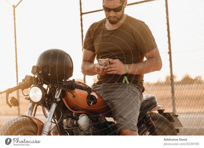 Mann sitzt auf Motorrad und surft mobil Smartphone moto ruhen benutzend Surfen Sonnenbrille fokussiert wehmütig sitzen Mobile männlich Feld Verkehr Straße