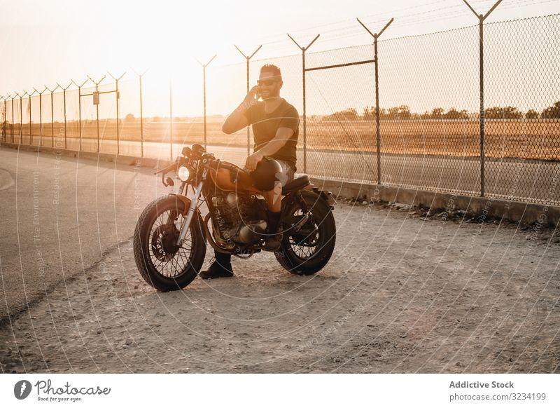 Mann sitzt auf Motorrad und surft mobil Smartphone moto ruhen benutzend sprechend Surfen Sonnenbrille fokussiert wehmütig sitzen Mobile männlich Feld Verkehr