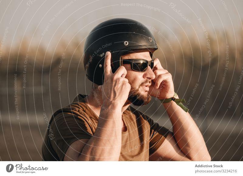 Nachdenklicher Mann mit Helm brutal Schutzhelm Vollbart Sonnenbrille besinnlich männlich Biker reisen Mitfahrgelegenheit Motor Stil Rennfahrer Motorradfahrer