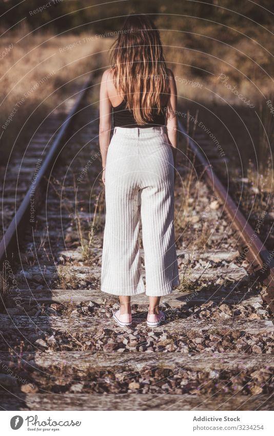 Langhaarige Frau steht auf mit trockenem Gras bewachsenen Eisenbahnen Straße reisen Nostalgie Reise Bahn Weg klassisch Passagier Tourismus Ausflugsziel Station