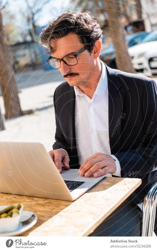 Älterer Mann benutzt Gadget beim Entspannen im Café benutzend Tablette digital klug Browsen zuschauend männlich älter gealtert Senior Apparatur Gerät arbeiten