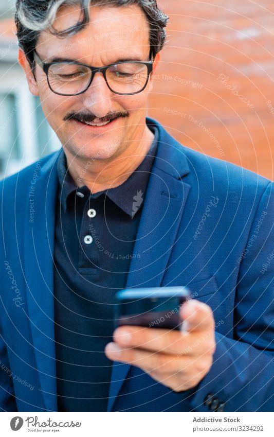 Senior-Geschäftsmann in blauer Jacke mit Smartphone Mann benutzend Browsen Surfen Mobile Telefon soziale Netzwerke zuschauend Texten Nachrichtenübermittlung
